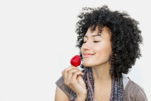 Woman smelling a strawberry